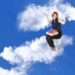 Happy red-haired girl with gifts in cloud dreams on a chair