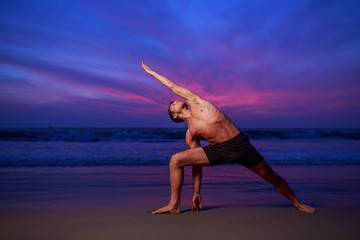 Man doing yoga stretch at sunset beach
