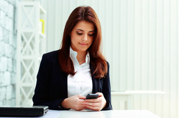 Young beautiful businesswoman typing on her smartphone in office
