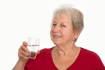 smiling elderly woman is drinking water