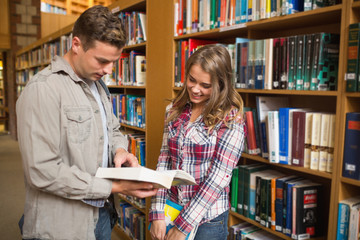 Happy classmates standing in library talking about a book