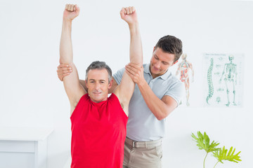 Male physiotherapist stretching a mature mans arms