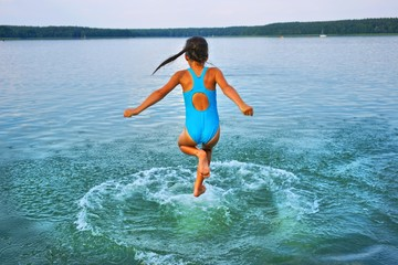 Girl leaping into lake, aged 10 years