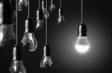 idea concept with broken bulbs and one LED glowing bulb