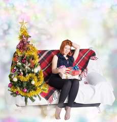 Happy girl on the sofa with a gift box in Christmas holidays