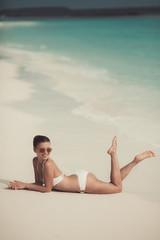 Happy beautiful woman in bikini standing near palm tree on tropi