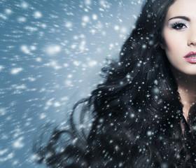 Portrait of a beautiful brunette woman on a snowy background