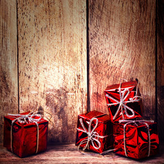 Christmas Red Gift Boxes with ribbon on rustic wood board with c