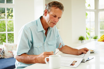 Middle Aged Man Reading Magazine Over Breakfast