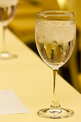 Glass with water and ice with golden color background