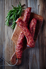 Dried sausage with rosemary on a chopping board