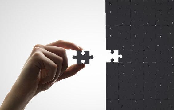 hand puts puzzle