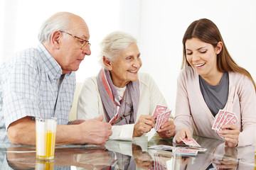 Family with senior couple playing cards