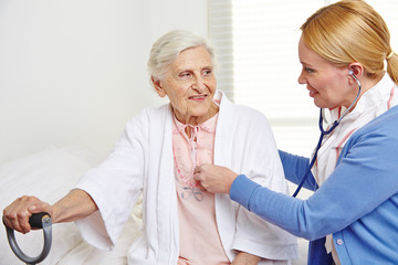 Geriatric nurse ausculting senior woman