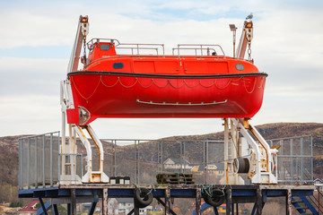 Red rescue boat stands on the coast in Norway