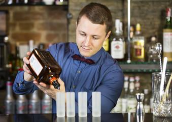 young man working as a bartender in a nightclub bar