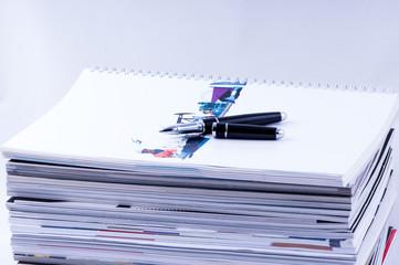 economics magazines with pen closeup