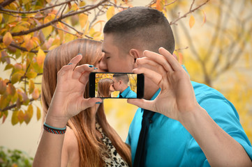 Couple Kissing While Taking Photo