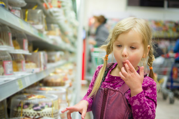 Adorable girl at shopping cart select sweet cakes in supermarket
