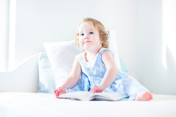 Adorable toddler girl with curly hair wearing a blue dress readi