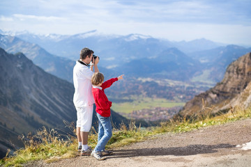 Young father and his teenager son taking pictures of a mountains