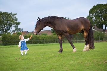 Cute little baby girl feeding a big horse on a ranch in autumn