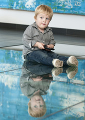 little child playing with cellphone and reflexion on the floor