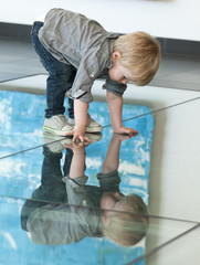 little child playing with his reflexion on the floor