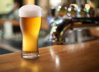 Photo of cold beer glass on a bar.