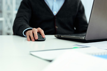 Closeup image of a casual businessman working on laptop