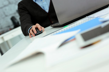 Closeup image of a man working at laptop at his workplace