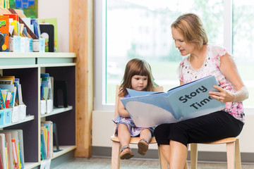 Teacher With Cute Girl Reading Book In Library