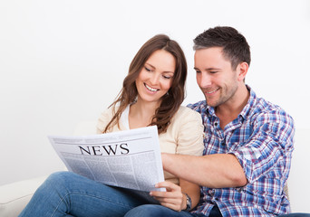Happy Young Couple Sitting On Couch Reading Newspaper