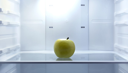 One apple in open empty refrigerator. Weight loss diet concept.