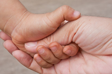 father's and baby's hands.