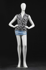 mannequin female dressed in shirt and shorts on black background