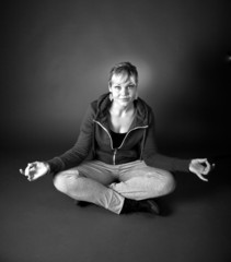 Studio portrait of a cute blond girl in a meditation position