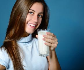 beautiful cheerful teen girl drinkink milk over blue