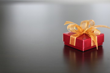 Red gift with golden ribbon on background