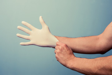 Health professional putting on surgical gloves