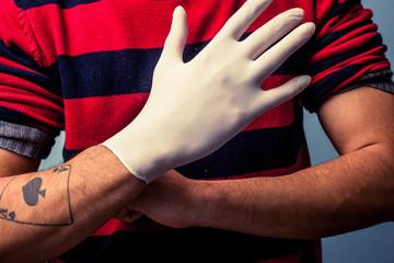 Tattoo artist putting on latex glove