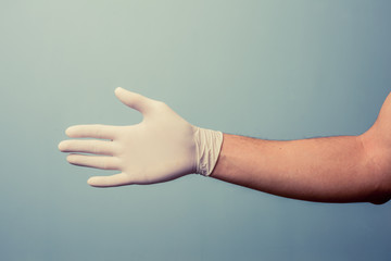 Hand wearing latex glove offering handshake