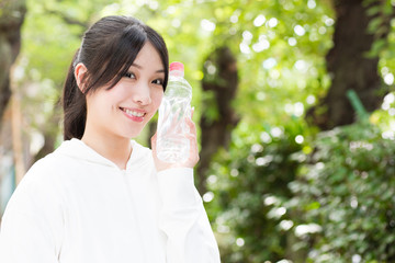 young asian woman holding bottle of water in the park