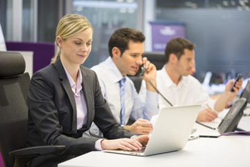 Pretty Businesswoman working on laptop, Businessman background