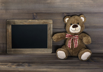 vintage style still life with teddy bear and blackboard
