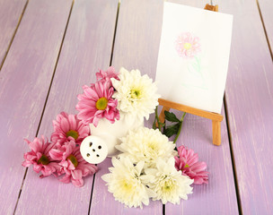 Composition of flowers and  small easel with picture