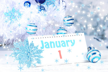 Calendar with New Year decorations on winter background