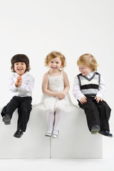 Little happy girl and two boys sit on white big cubes on white
