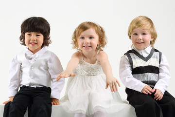 Little girl and two boys sit on white big cubes on white