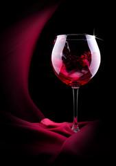 glass of splashing wine with red silk